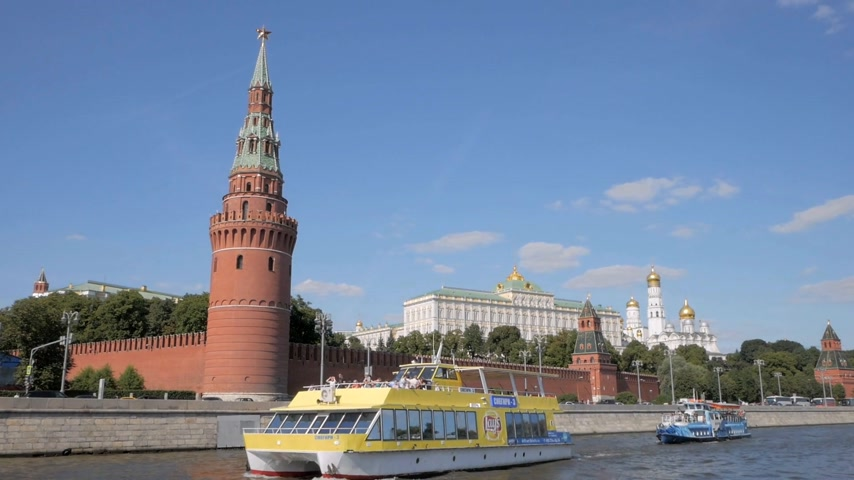 MOSCOW - AUGUST 17, 2018: Tourist ships sailing past red brick Kremlin walls, towers and beautiful white churches in Moscow, Russia