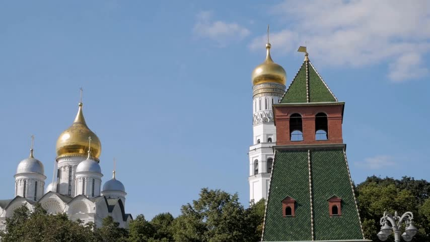 Close up view on Kremlin tower and beautiful white cathedrals with golden domes against blue sky in Moscow, Russia