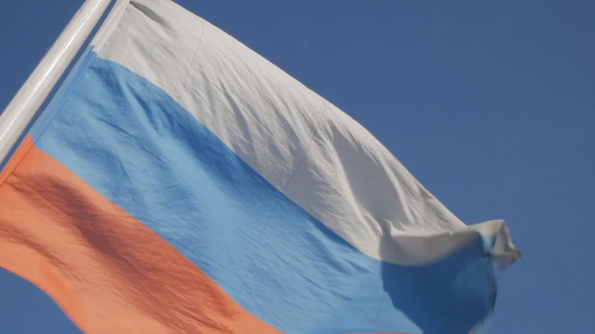 Close up of flying banner of Russian Federation against blue sky