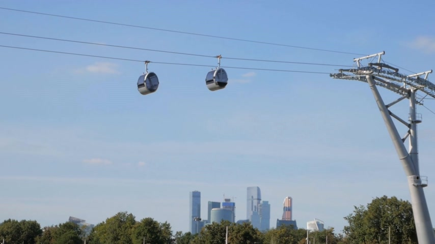 Cable road cabins slowly moving in the air over Sparrow Hills park with Moscow City district in background Stock Footage
