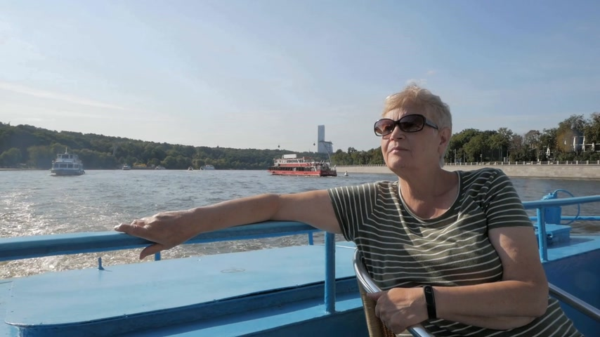Relaxed mature woman enjoying tourist boat trip along the river