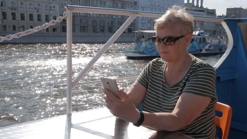 Mature woman sitting on tourist ship and holding smartphone with sparkling water and tourist boat passing behind on sunny summer day Stock Footage