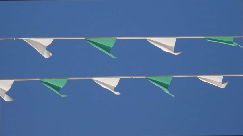 Lines of moving green and white bunting festive flags against blue sky