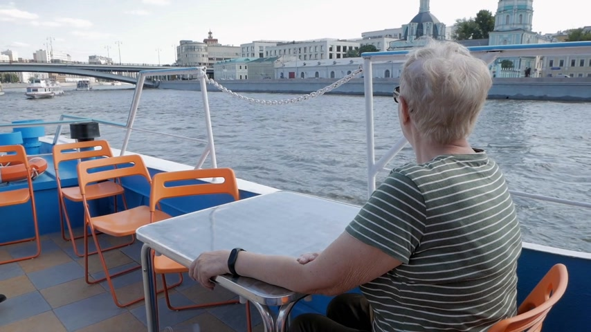 Back view of mature woman on tourist boat observing beautiful view on Moskva river and its embankment