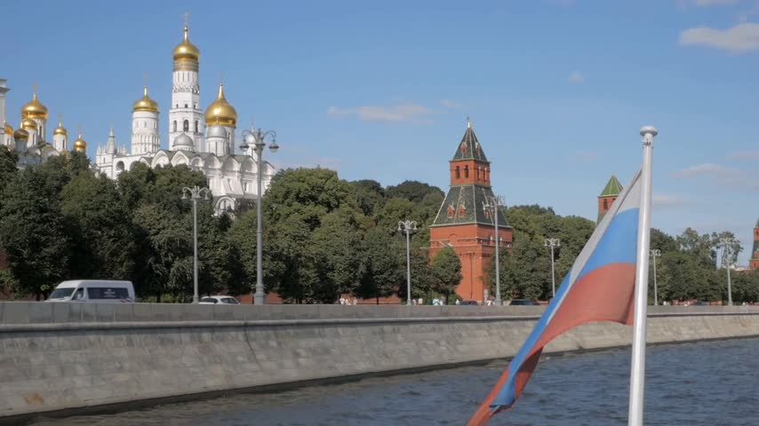 Russian flag on boat in front of red brick Kremlin walls, towers and white churches with golden domes on summer day in Moscow, Russia