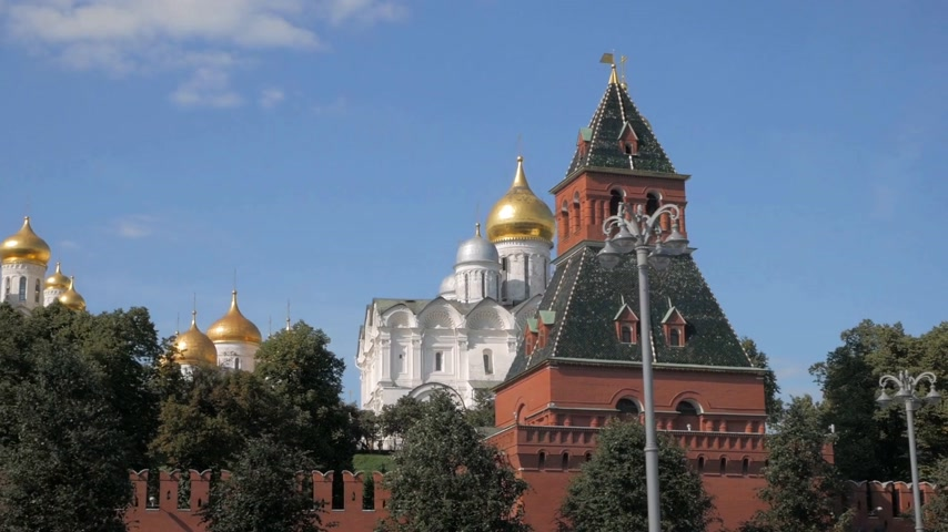 View on red brick Kremlin walls, one of its towers, green trees, and beautiful white cathedrals with golden domes against blue sky in Moscow, Russia