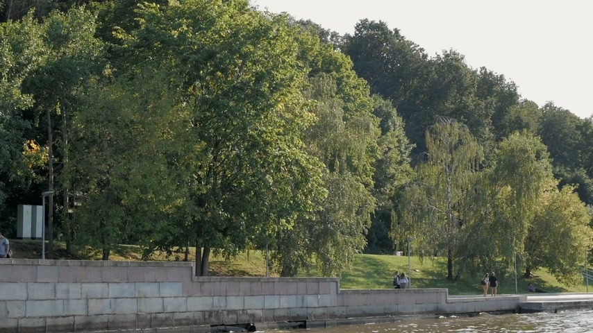Beautiful Moskva river embankment on Sparrow Hills with lush green trees and people relaxing in Moscow, Russia