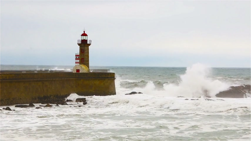 kasırga : Strong waves break on the pier, the lighthouse on the shore of the Atlantic Ocean Stok Video