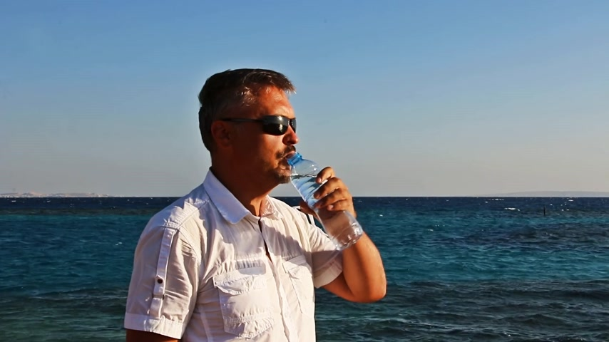 man leisurely drinks water from a bottle