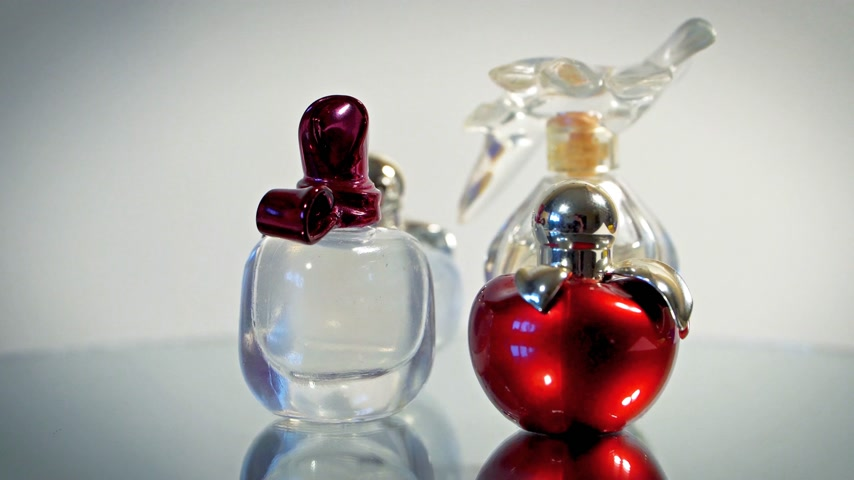 darling : Modern glass perfume bottles rotate on white background. Stock Footage