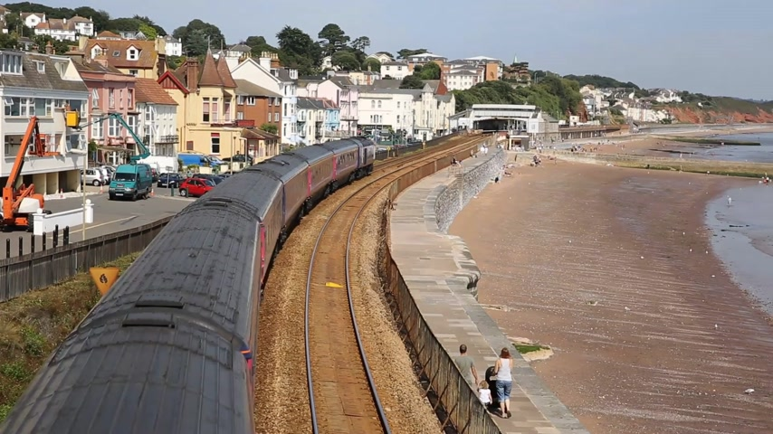 lokomotif : Train travelling away from camera viewed from bridge on railway bordering sand and sea Dawlish Devon England