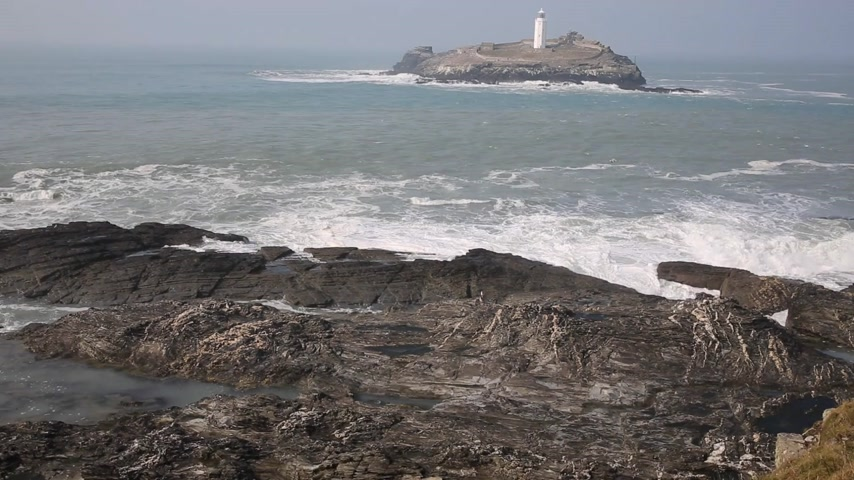 batı : Lighthouse and island with sea breaking over rocks Godrevy Cornwall England UK