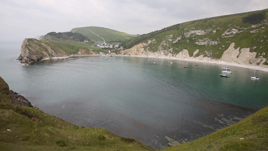 jura : Lulworth Cove Dorset with boats in the natural harbour, top tourist attraction on English Jurassic Coast and Englands first natural World Heritage Site