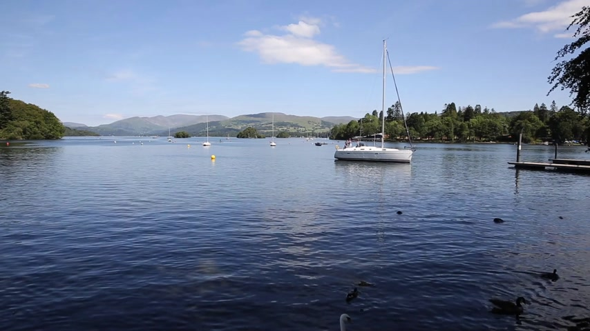 huzurlu : Beautiful peaceful relaxing summer day in the English Lake District Bowness Windermere England uk with a boat at this popular tourist location