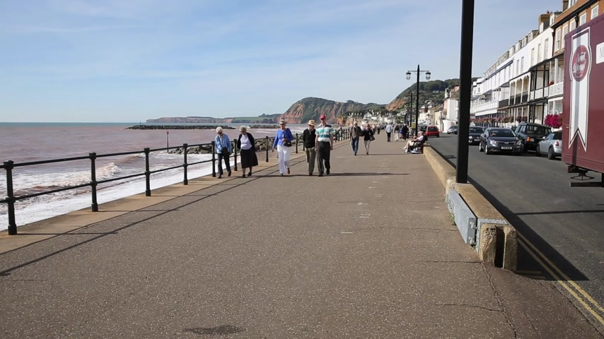 İngilizce : People walking Sidmouth seafront Devon England UK traditional English tourist town Stok Video