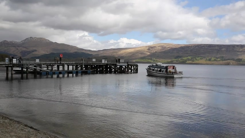 argyll : Loch Lomond Scotland UK in summer with boat arriving at the jetty Scottish tourist destination Stock Footage