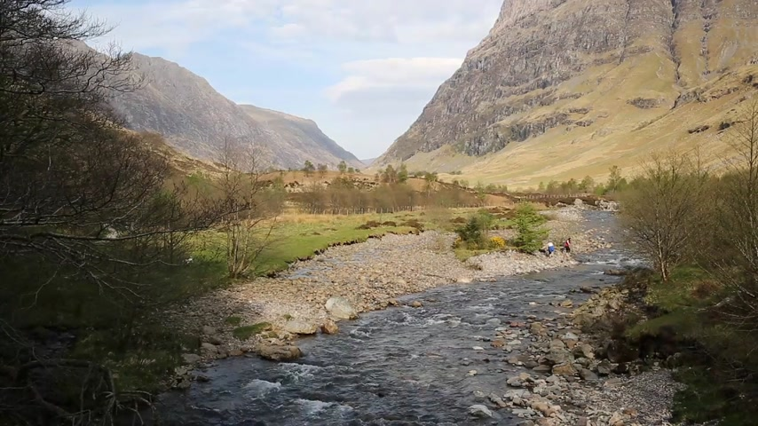 coe : Scottish glen with river Glencoe Scotland UK with mountains in Highlands in spring with people Stock Footage