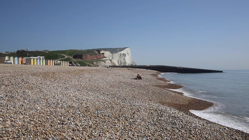 Seaford beach with people sunbathing and waves with chalk cliffs in background East Sussex UK