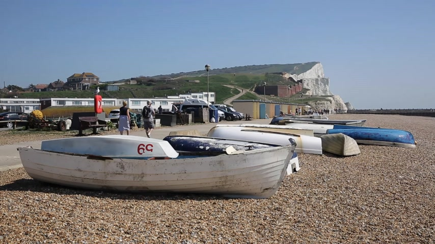 к юго западу : Seaford East Sussex with boat and white chalk cliffs and visitors walking in the sunshine on the seafront promenade