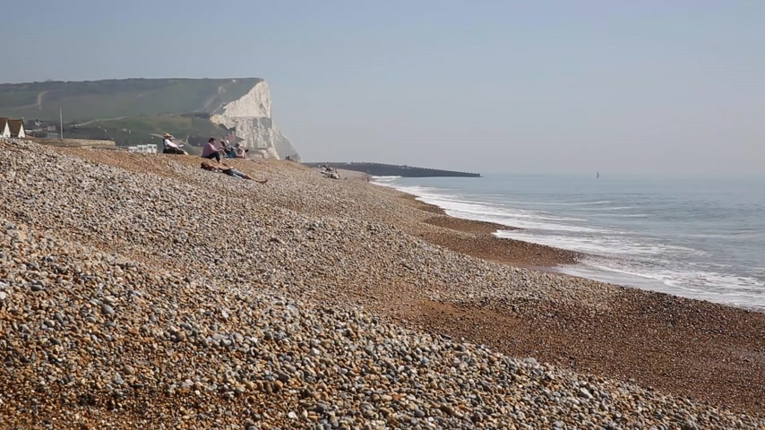 к юго западу : Seaford beach with people sunbathing and waves with chalk cliffs in background East Sussex UK