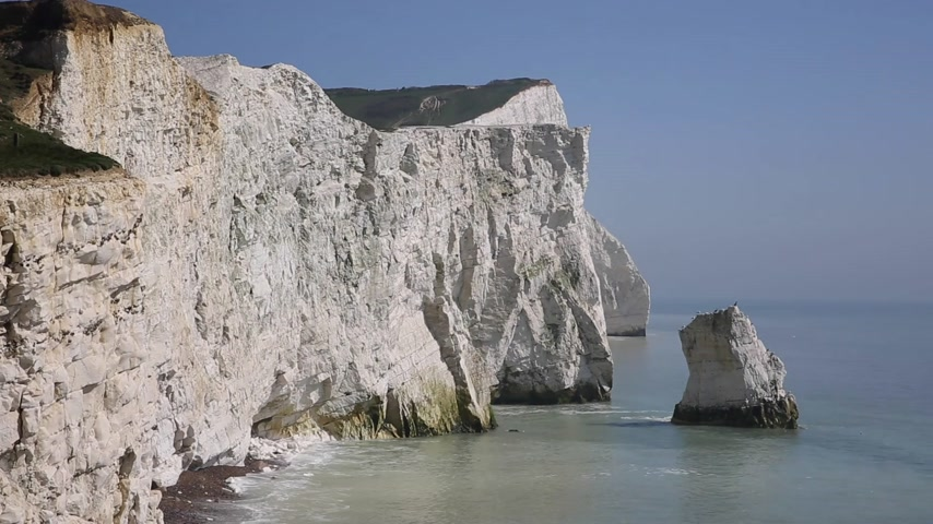 Beautiful white chalk cliff stack Seaford East Sussex England UK near Seven Sisters with waves lapping cliffs and blue sea and sky