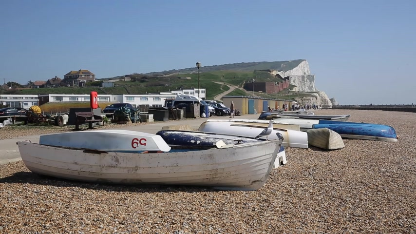 Seaford East Sussex with seagulls boat and white chalk cliffs and visitors walking in the sun