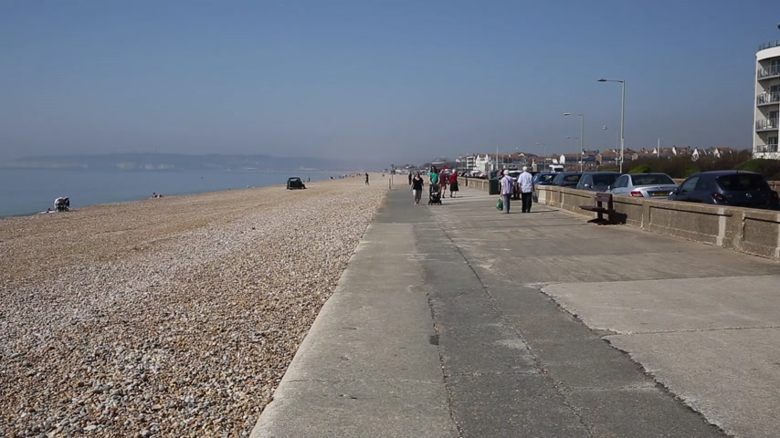 Seaford East Sussex with people enjoying the spring sunshine walking on the seafront promenade
