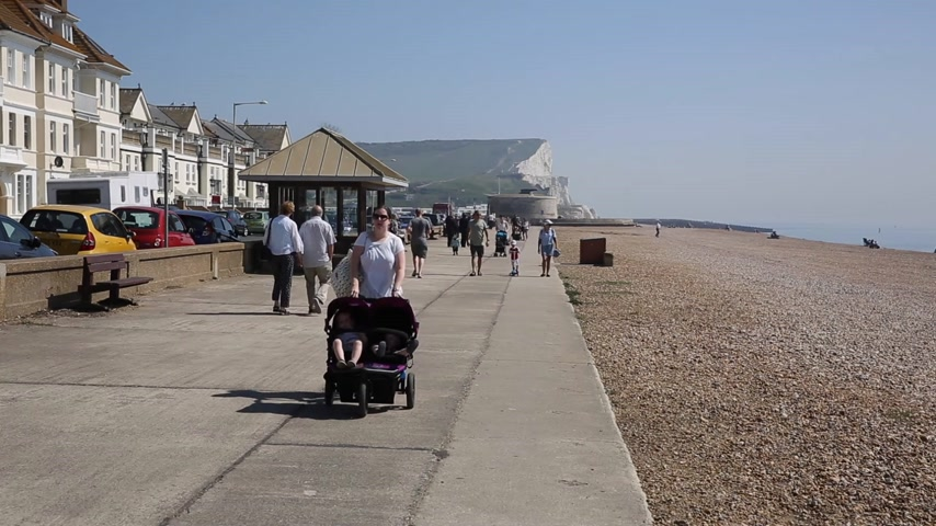 stacks : Seaford East Sussex with visitors walking in the sunshine on the seafront promenade
