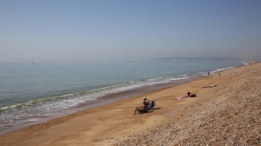 Seaford Beach con personas en tumbonas, tomar el sol y las olas East Sussex UK