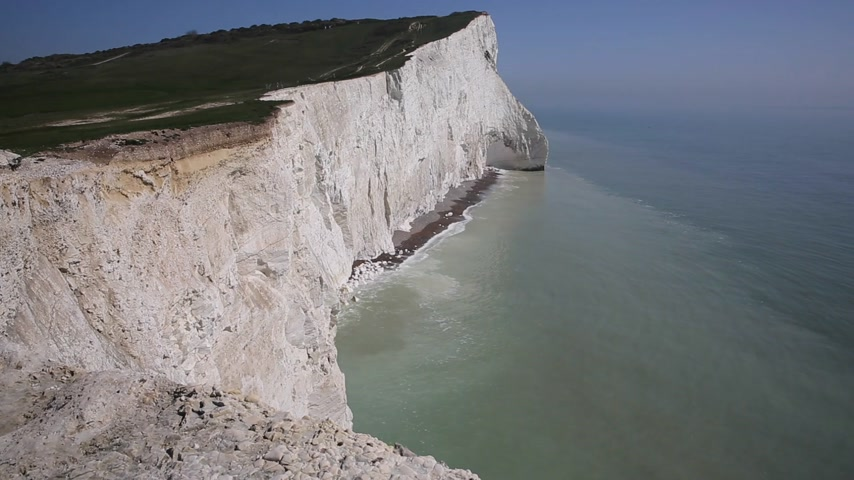 Beautiful English coastline Seaford East Sussex England uk with white chalk cliffs, waves and blue sky