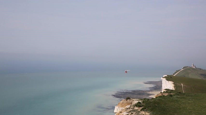 Coastguard rescue helicopter patrols the coast near Beachy Head East Sussex England UK Stock Footage