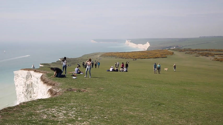 Hombre cerca del borde y mirando por encima a Beachy Head East Sussex Archivo de Video