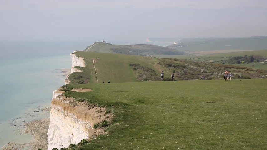 Camino de la costa hacia el faro de Belle Tout entre Beachy Head y Seven Sisters East Sussex con gente caminando Archivo de Video