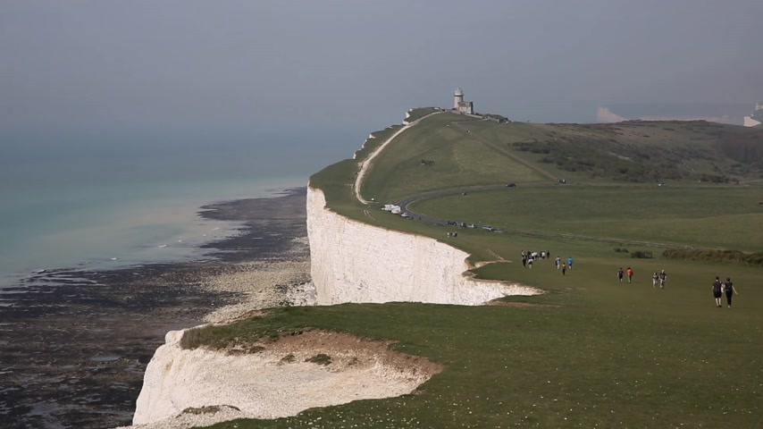 Coast path along chalk cliffs between Beachy Head, Birling Gap and Seven Sisters East Sussex with visitors walking
