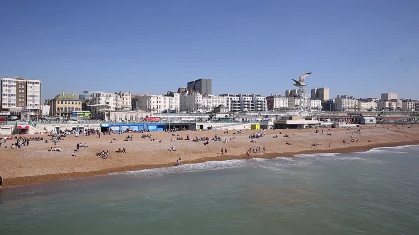 Brighton beach busy with visitors and tourists in beautiful spring weather in East Sussex UK pan
