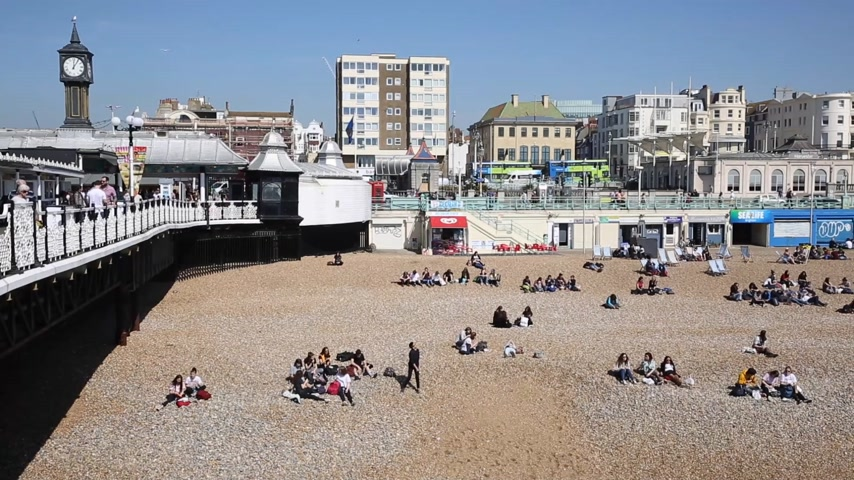 Brighton beach busy with people pan view beautiful spring weather in East Sussex UK Stock Footage