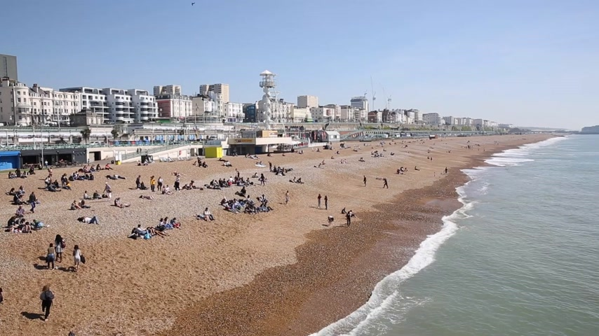 Brighton playa y costa East Sussex Inglaterra Reino Unido con gente disfrutando del sol de primavera Archivo de Video