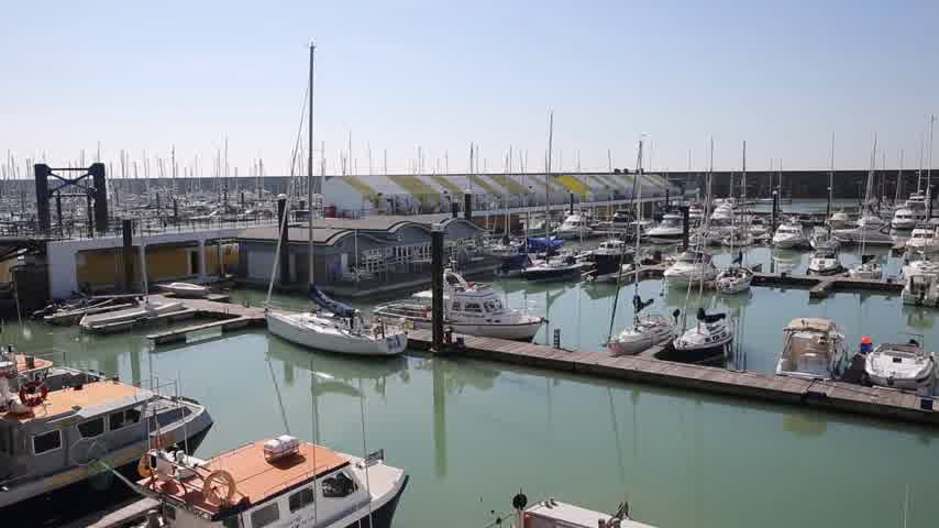 Brighton marina boats and yachts and apartments on a beautiful day in East Sussex England UK pan view