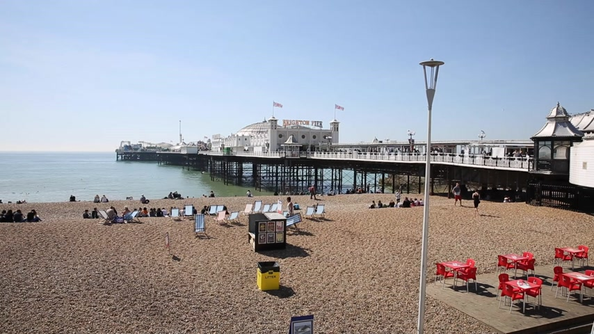 Brighton beach and pier busy with visitors in fine weather