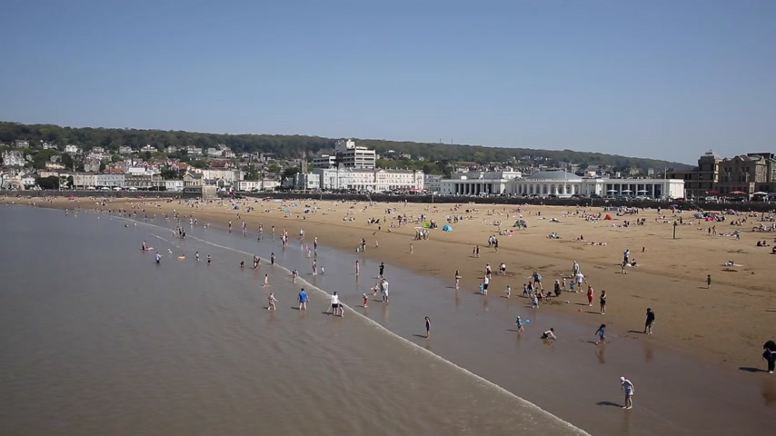 Weston-super-mare beach and seafront busy with people in the sea on May bank holiday 2018 Stock Footage