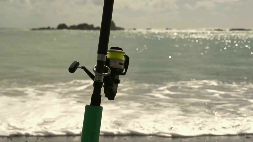 fishermen : Bay of Islands, New Zealand. Fishing rod in rod holder on the beach. Shallow depth of field.