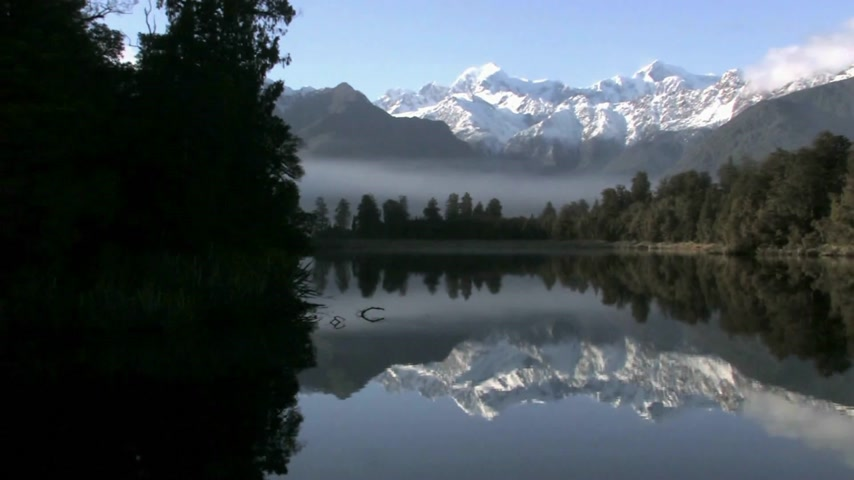 göl : Franz Josef, New Zealand.  Pan shot across Lake Matheson on the west coast of New Zealand, Famous for reflecting a near-perfect image of Aoraki Mount Cook in its waters Stok Video
