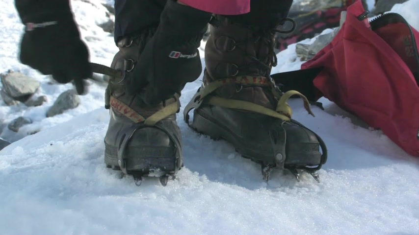alpinista :  Young female putting on crampons before walking on the Fox Glacier, which is situated on the west coast of the South Island