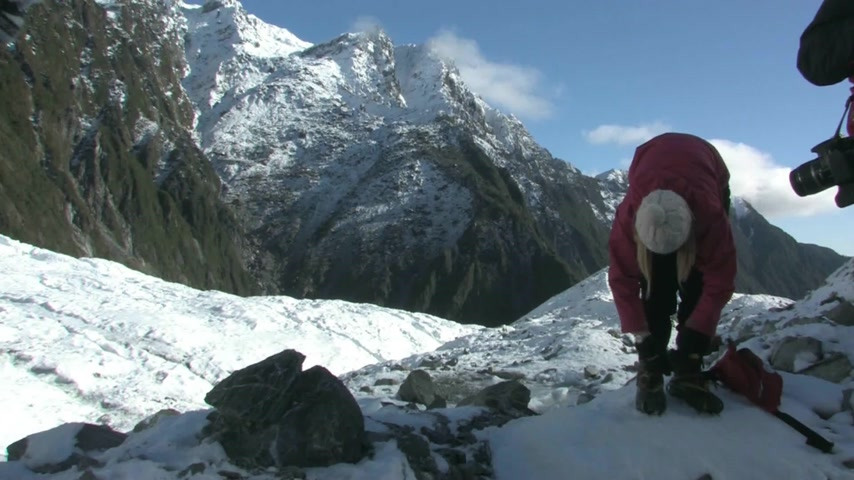 alpinista : Young female putting on crampons before walking on the Fox Glacier, which is situated on the west coast of the South Island Stock Footage