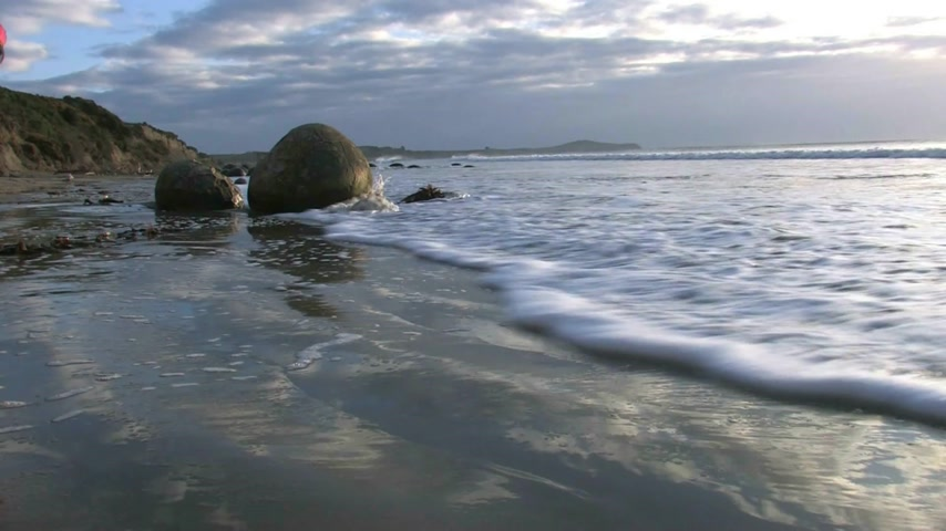 "surfovat : The Moeraki Boulders are a group of very large spherical ""stones"" on Koekohe Beach near Moeraki on New Zealand's Otago coast. These boulders are actually concretions that have been exposed through shoreline erosion from coastal cliffs"