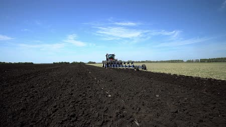 plowed land : Land cultivation. Tractor prepares land for sowing.
