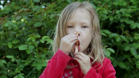 леденец : Little cute girl playing with a stick from a popsicle and looking at the camera.