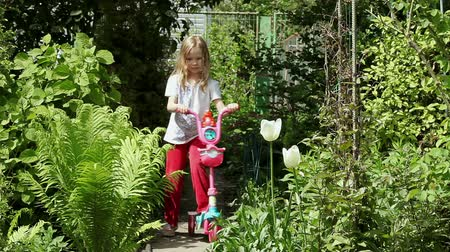 skútr : The little cute girl riding her scooter along the path in the garden Full length Dostupné videozáznamy