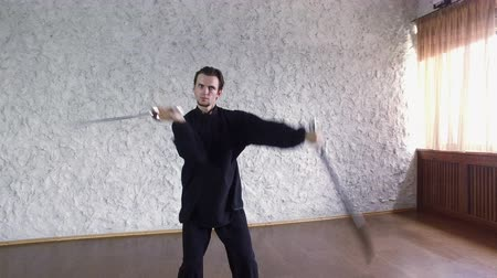 quimono : Man practicing elements of tai chi. A man rotating steel swords around a body 4K Vídeos