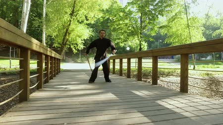 quimono : Training in the park. Man practicing elements of tai chi. The young man rotating steel swords around his body. 4K